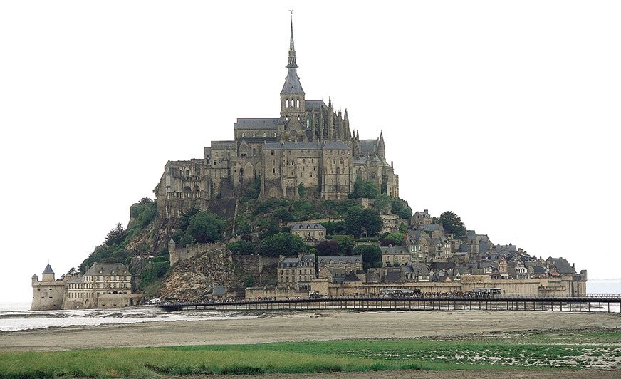 Mont Saint-Michel. Jest to bardzo stare opactwo wraz zmiasteczkiem, wybudowane na wyspie, które zlądem połączone jest wąską groblą, ale tylko wczasie silnych przypływów.